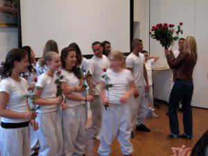 Uddeler roser på integrationsseminar